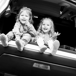 two happy kids in the car  ( black and white )