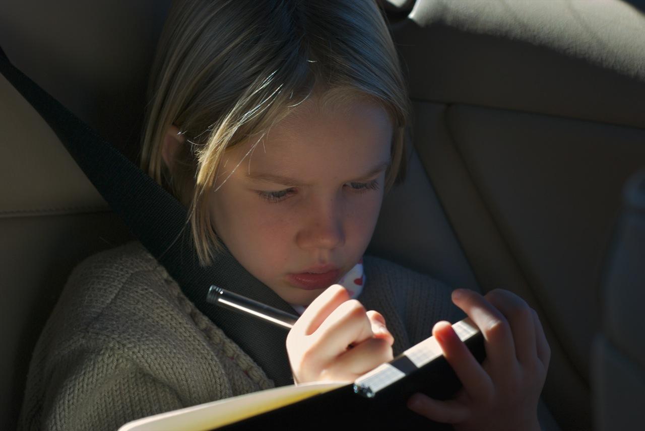 child logging memories in a journal